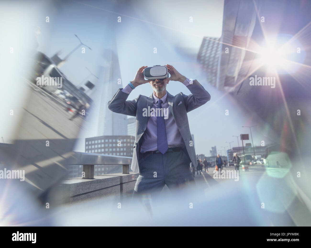 Businessman using virtual reality simulator glasses on urban street, London, UK - Stock Image