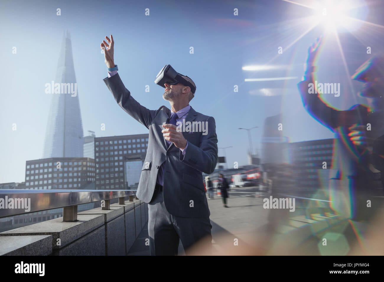 Businessman using virtual reality simulator glasses, reaching for sky on sunny urban bridge, London, UK - Stock Image