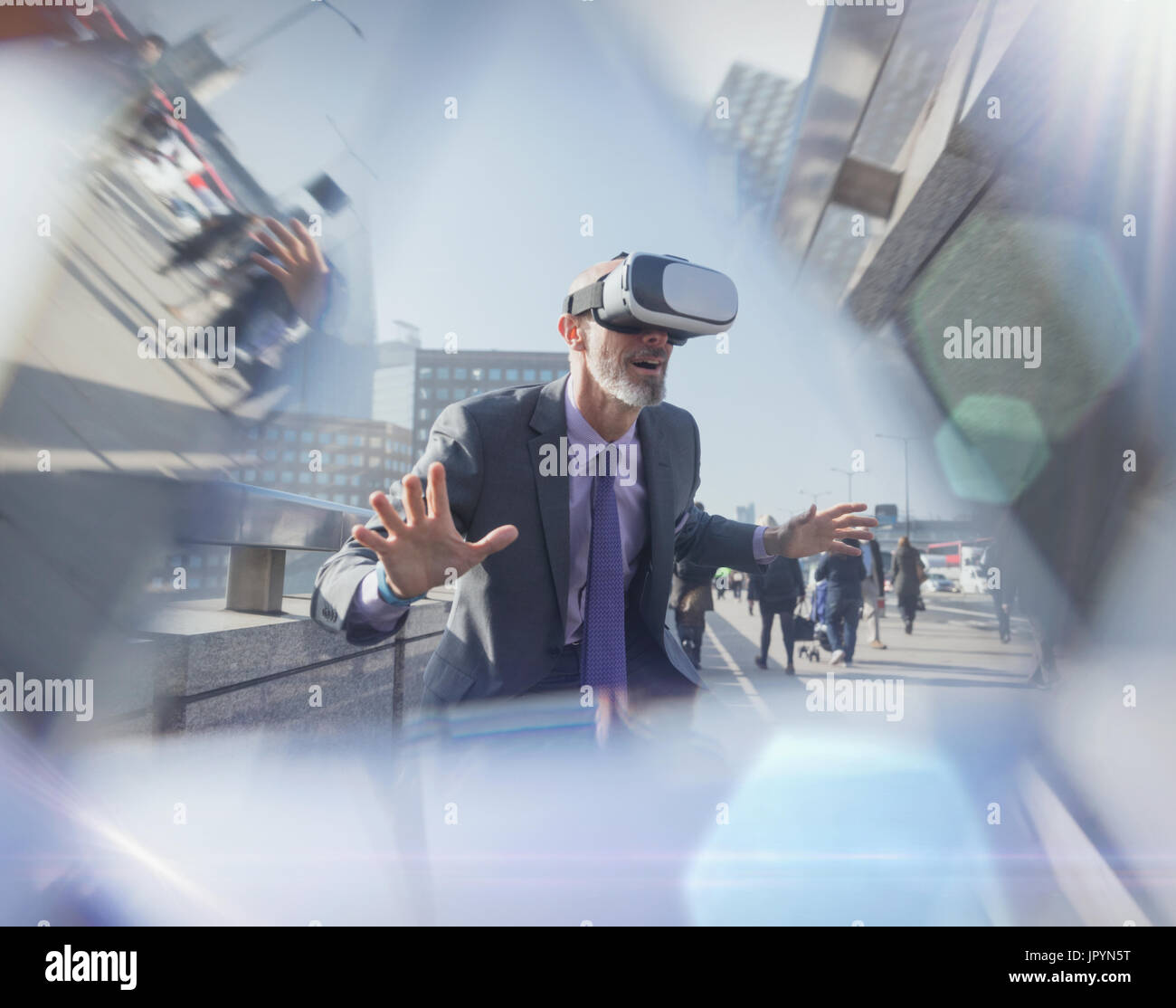 Businessman using virtual reality simulator glasses on urban bridge - Stock Image