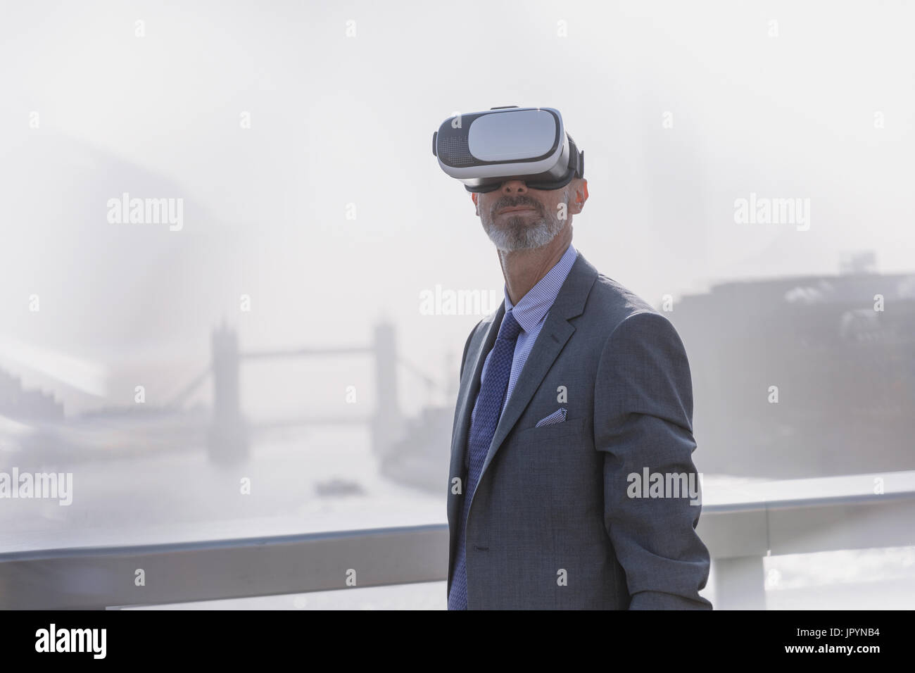 Businessman using virtual reality simulator glasses on sunny urban bridge over Thames River, London, UK - Stock Image
