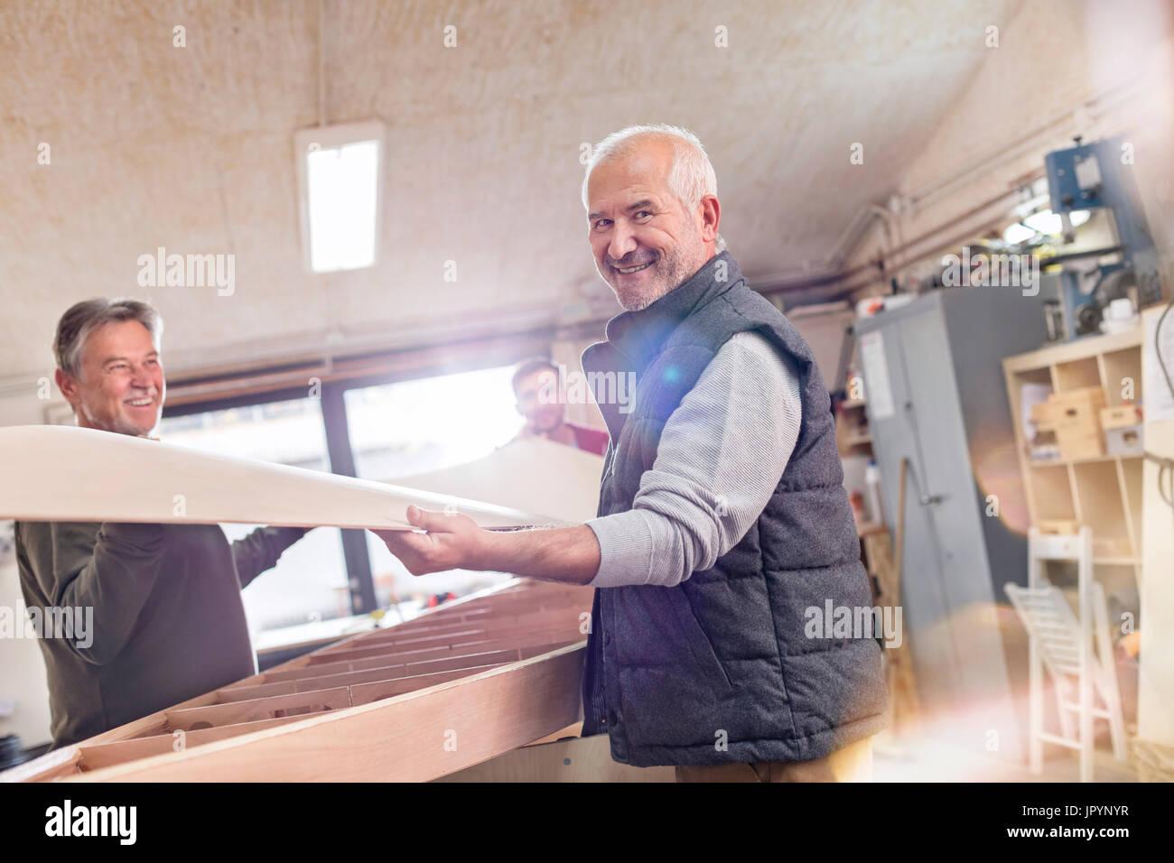 Portrait smiling senior male carpenter lifting wood boat in workshop Stock Photo
