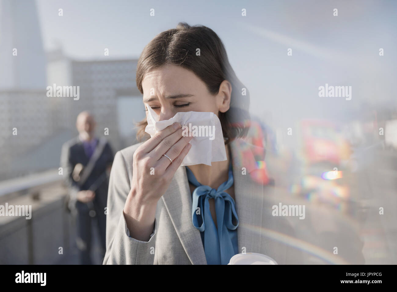 Businesswoman with allergies blowing nose into tissue on sunny urban sidewalk - Stock Image