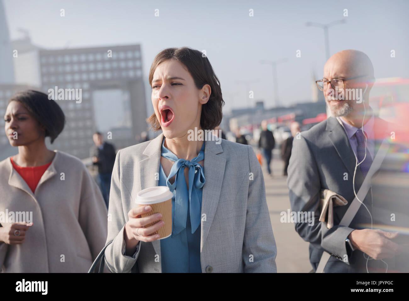 Tired businesswoman with coffee yawning on sunny morning urban pedestrian bridge - Stock Image