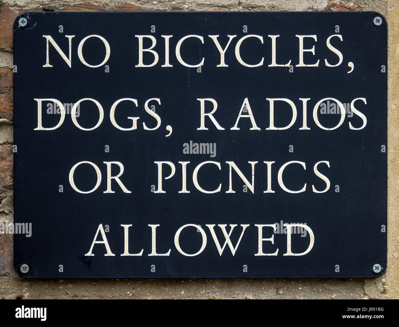 Cambridge College Restrictions Sign - No Bicycles, No Dogs, No Radios and no Picnics allowed in the college grounds - Stock Image