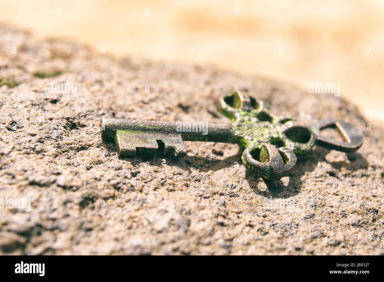 Treasure key lost on rock at the beach. Opportunity or Mystery concept. - Stock Image
