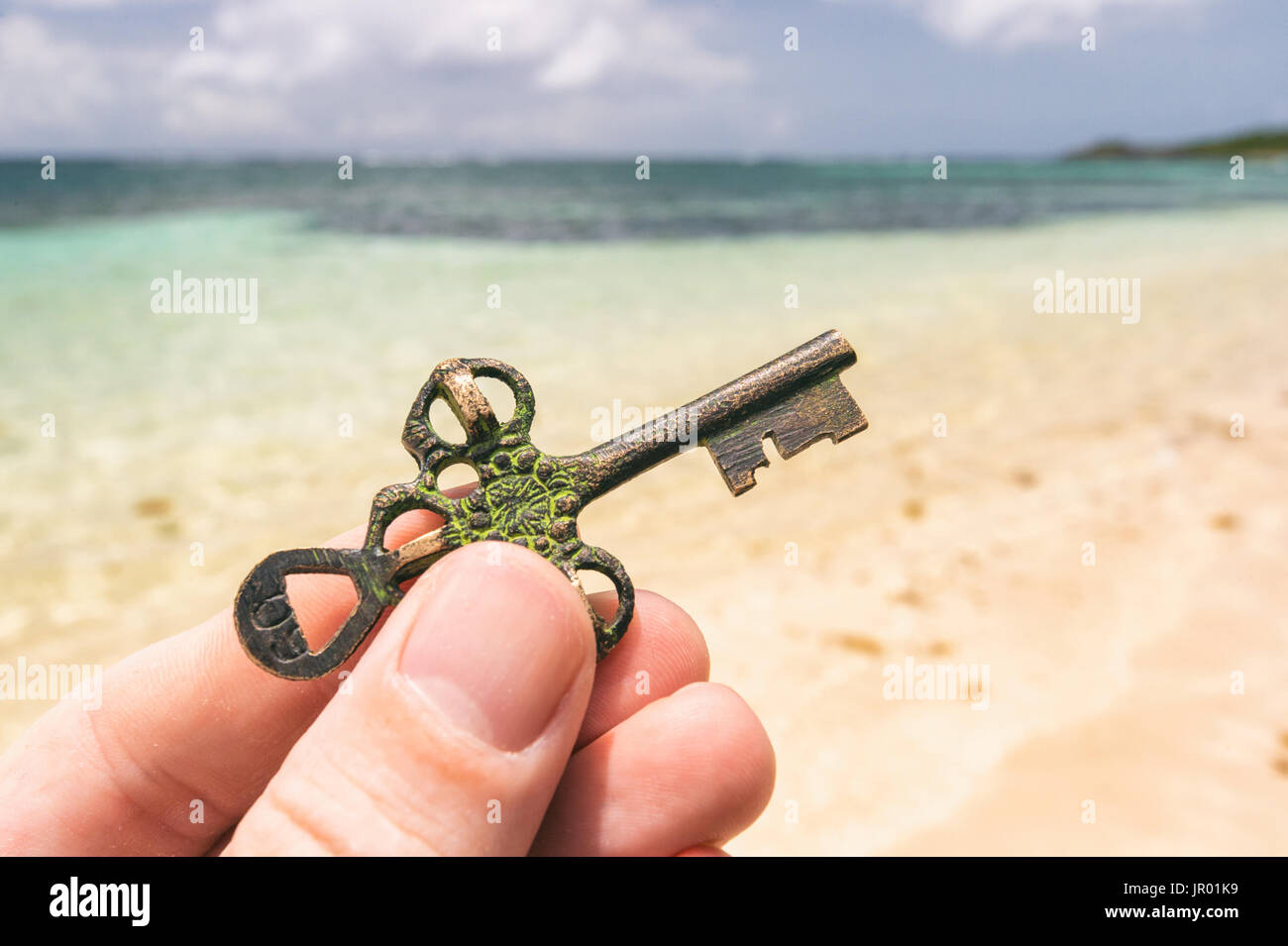 Hand holding a Treasure key found on a tropical beach. Opportunity or Mystery concept. - Stock Image
