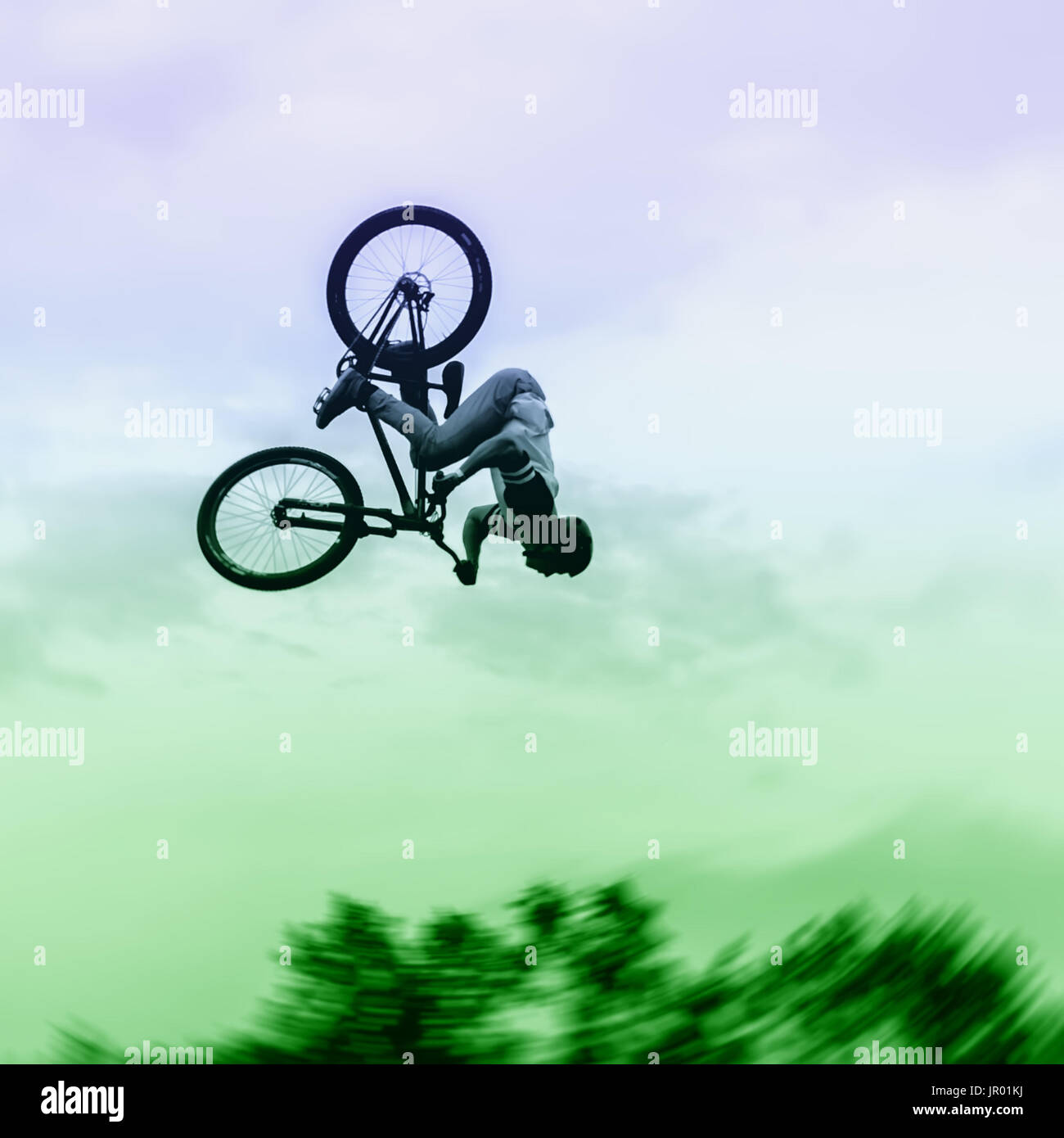 Silhouette of unidentified young man performs stunts on background of vivid sky. Extrem Sport and risk Stock Photo