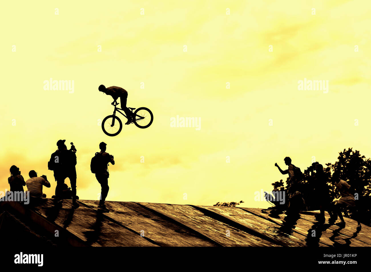 Extrem Sport and risk. Performance at competitions. Silhouette of unidentified young man performs stunts on background of vivid yellow sky. - Stock Image