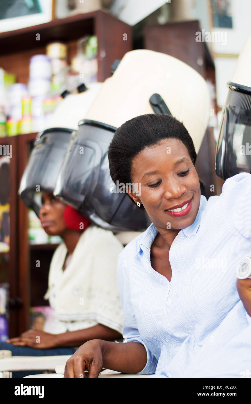 This smiling young woman sitting nextto her girlfriend under the helmet , consults her watch . Stock Photo