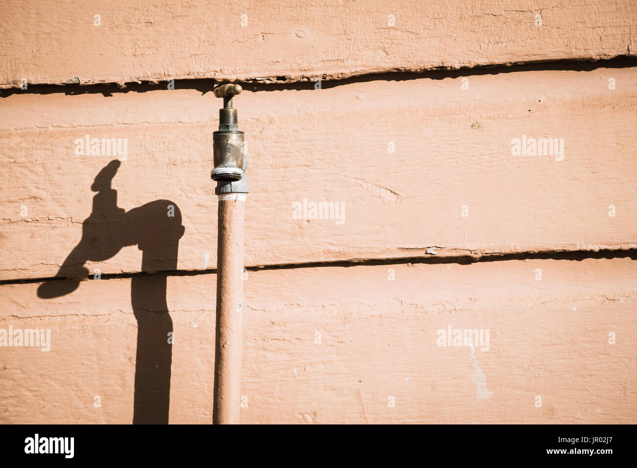 A single spigot or tap or faucet up against a timber wall in direct sunlight - Stock Image