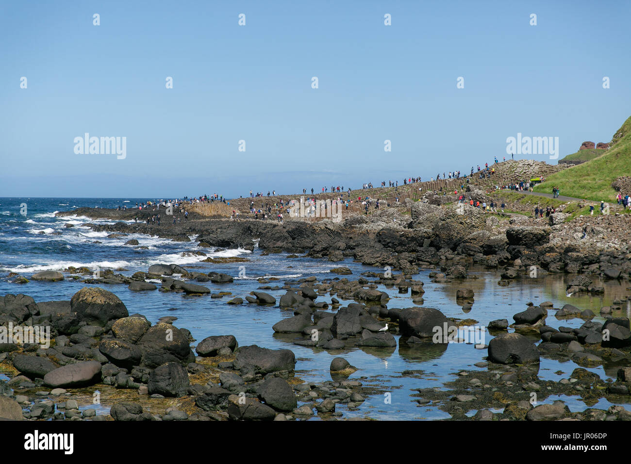 View on the Giant`s Causeway coast stretching out to the Atlantic ocean occupied by tourists and visitors Bushmills Antrim Northern Ireland Stock Photo