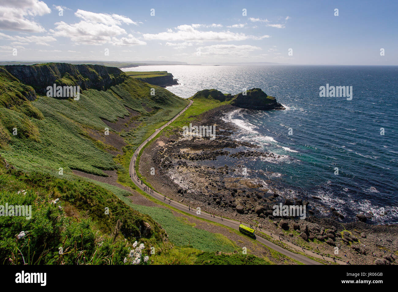 View from the cliff above the road with tourists leading to Giants Causeway one of Europe's most magnificent coastlines in Antrim Northern Ireland - Stock Image