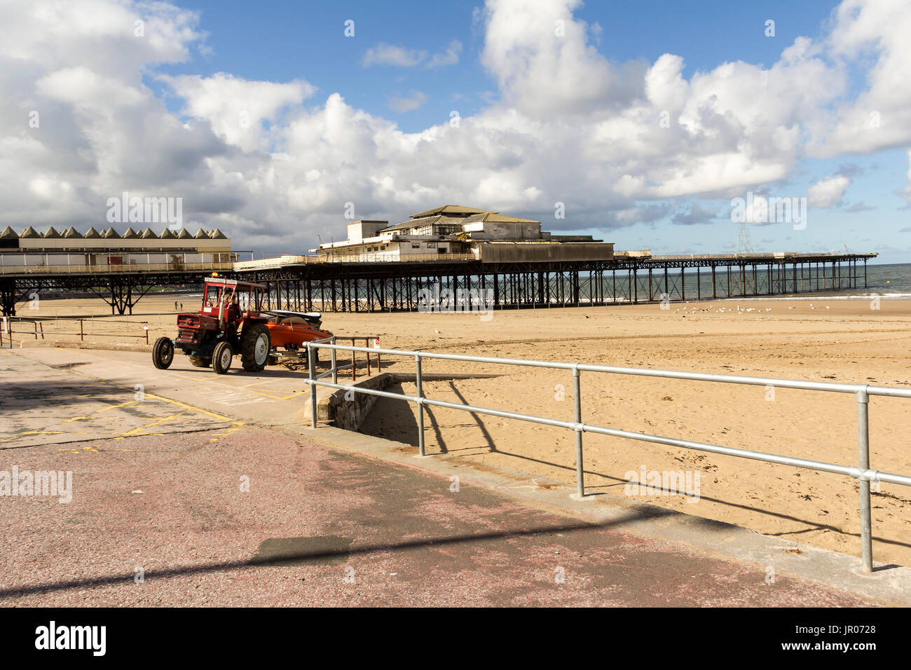 Tractor leaving the beach after cleaning the area, with Victoria Pier in the background in Colwyn Bay, north Wales.  The image was taken 14 Sept 2013 - Stock Image