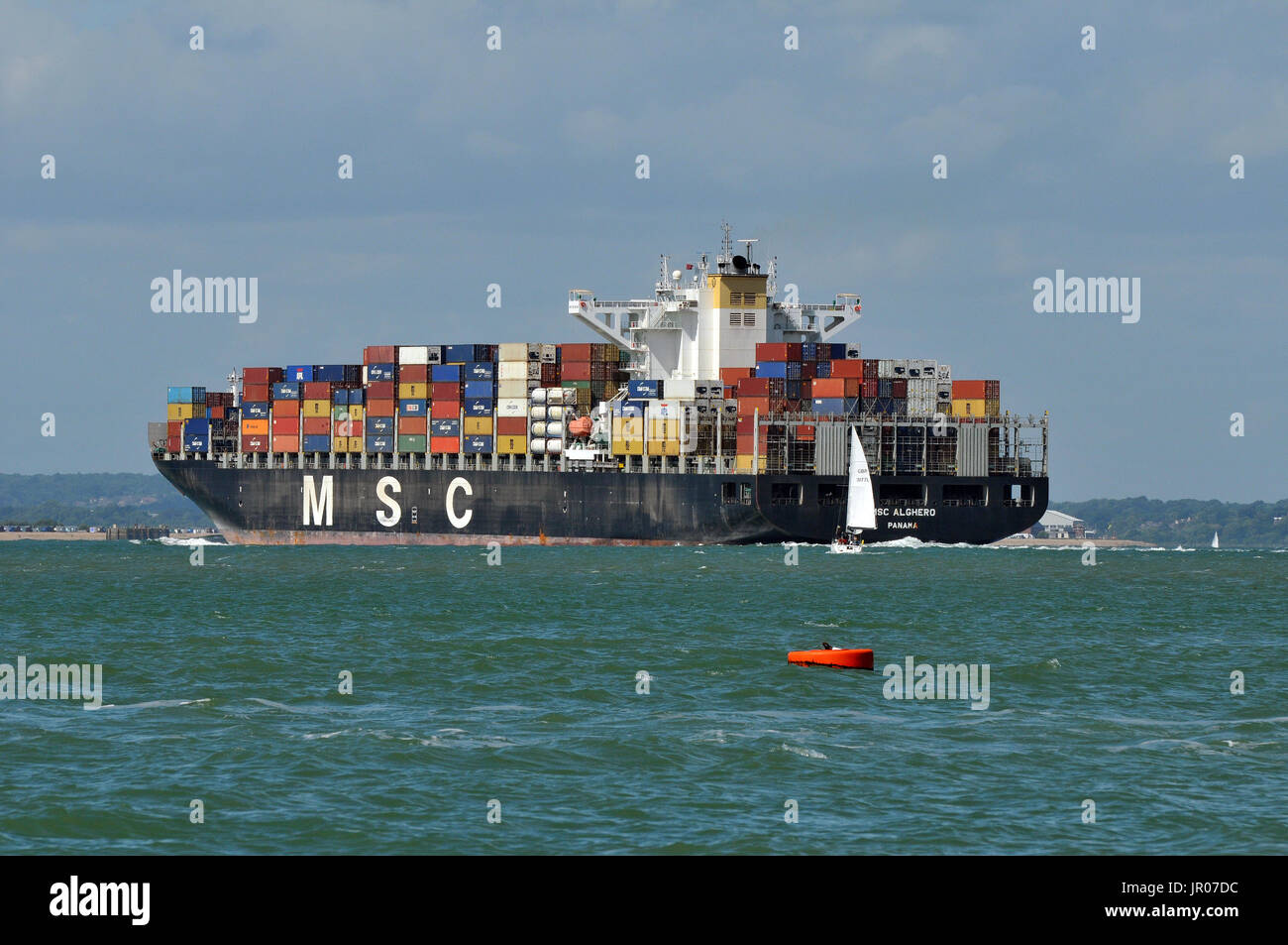 a large container ship entering Southampton port or harbour during cowes week close to some racing yachts off of the isle of wight on the sea solent - Stock Image