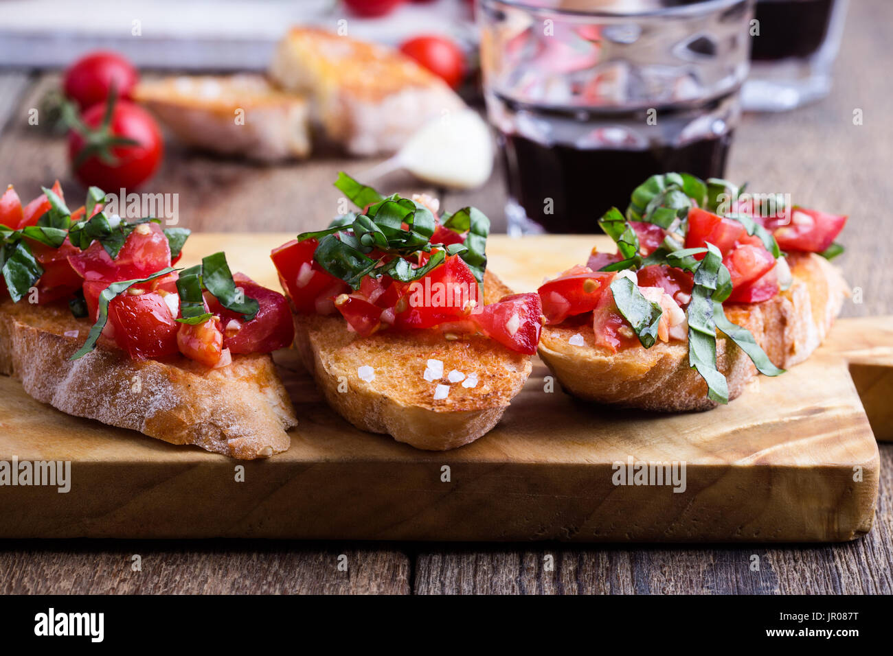 Tomato and basil bruschetta with toasted garlic bread, traditional Italian appetizer on rustic wooden cutting board - Stock Image