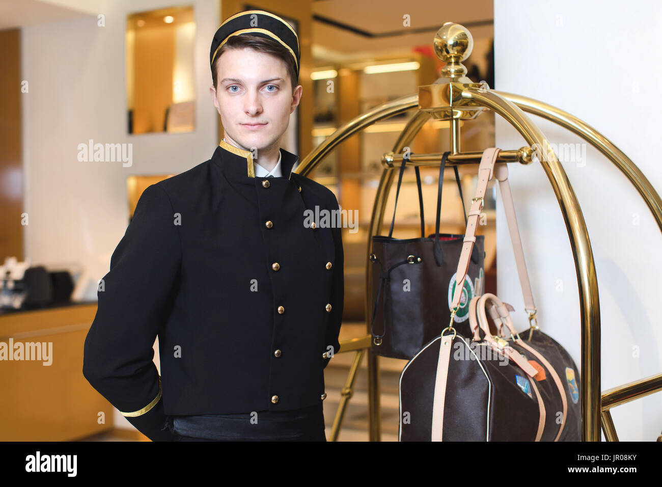Young man in uniform serving in hotel - Stock Image