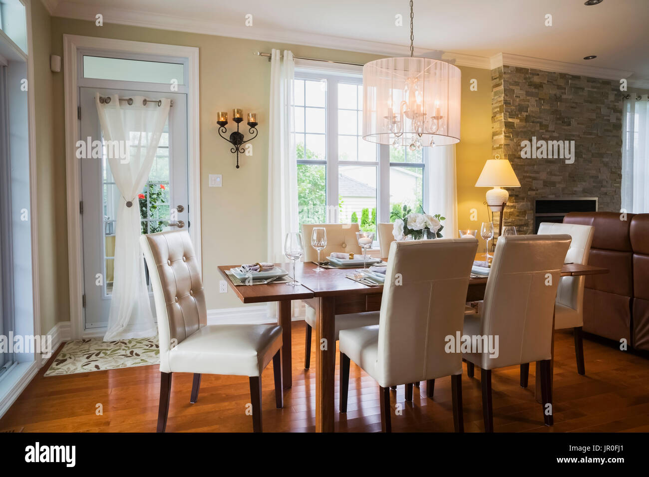 Dark Stained Oak Wood Table With White High-Back Leather And Wood Chairs In The Dining Room Inside A Contemporary Country Style Residential Home - Stock Image
