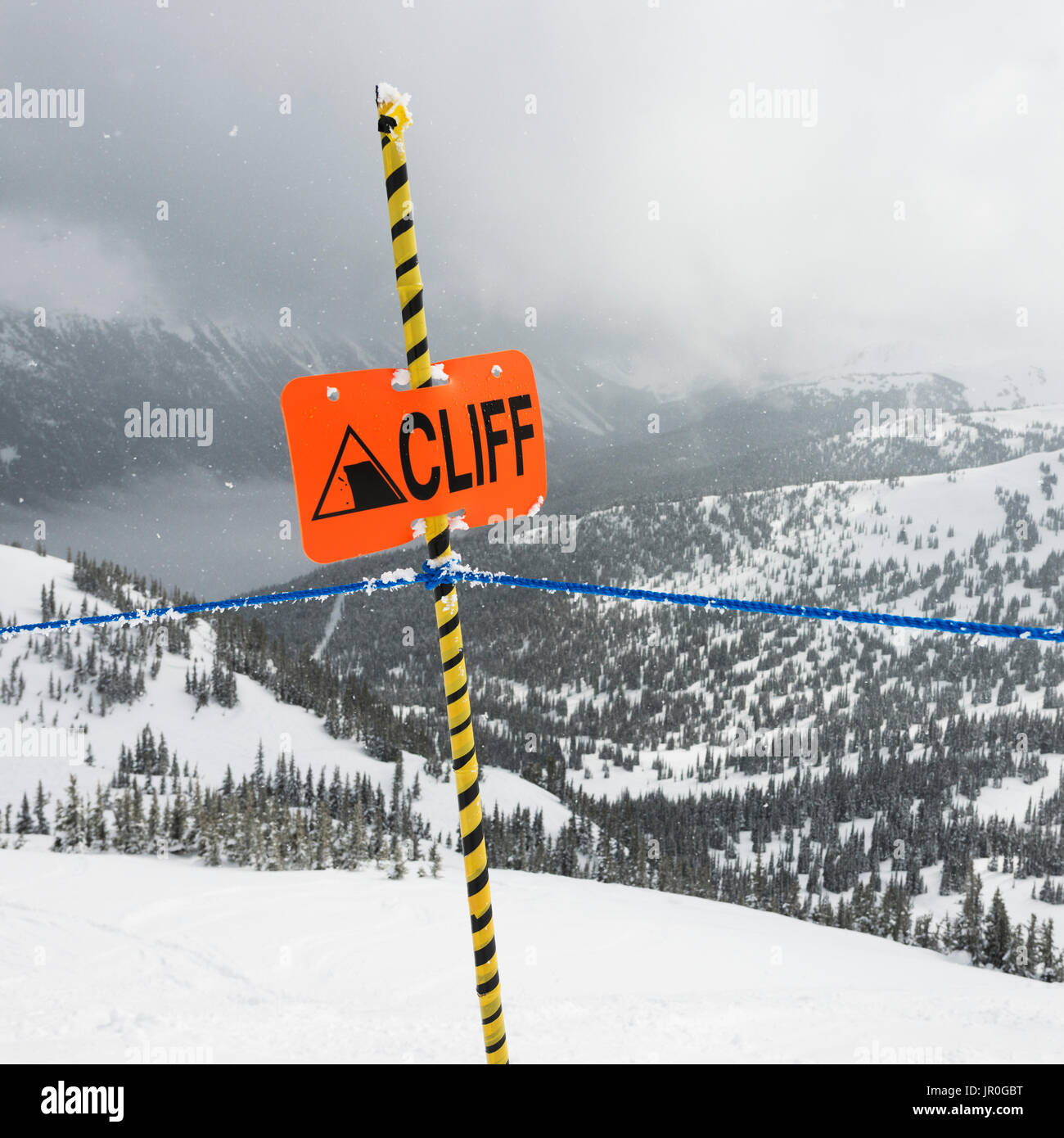 A Caution Sign At A Ski Resort Warning Of A Cliff; Whistler, British Columbia, Canada - Stock Image