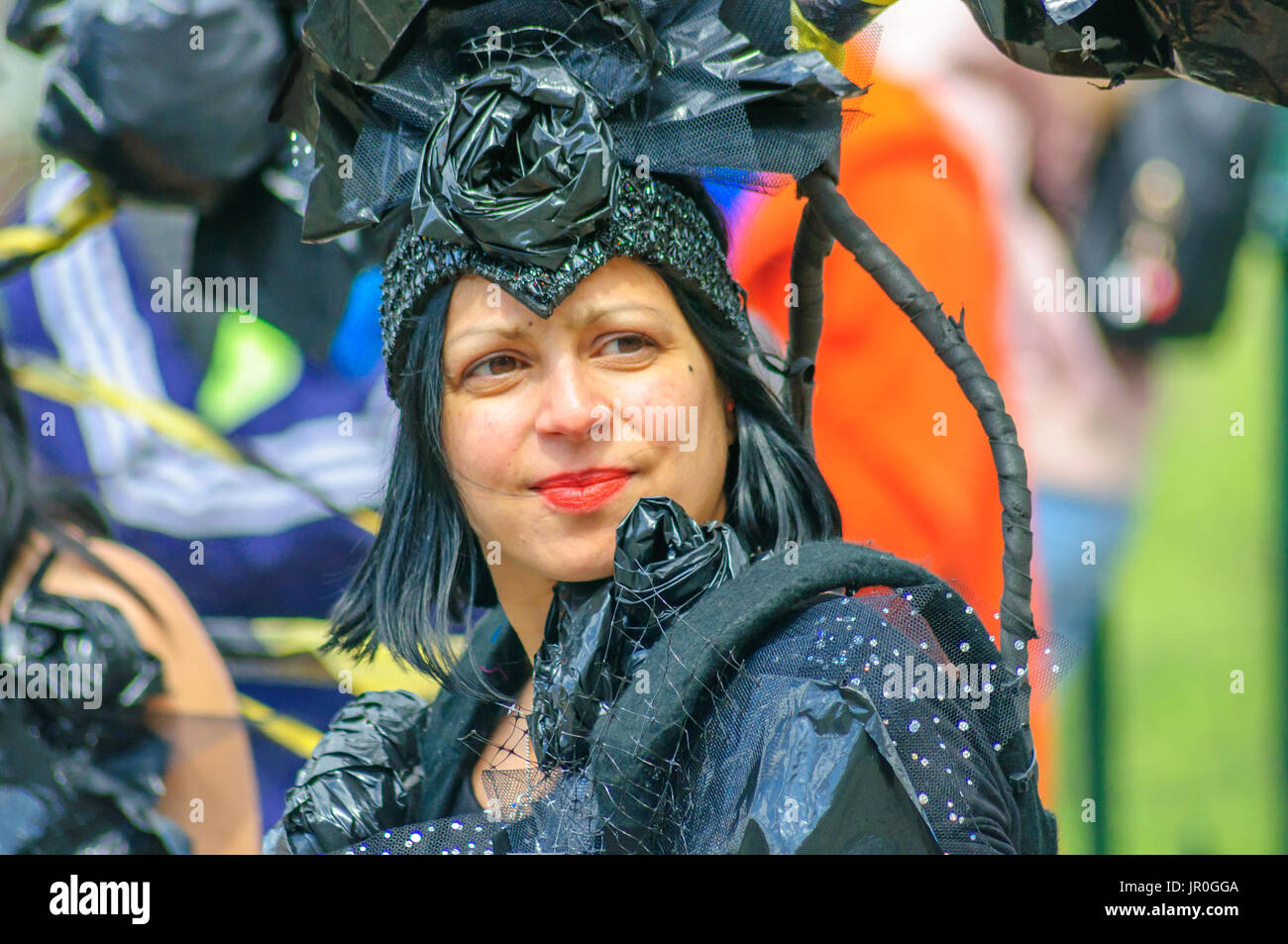 Female performer wearing a black costume and headdress in the parade on the streets of Edinburgh in the Carnival of The Jazz and Blues Festival - Stock Image