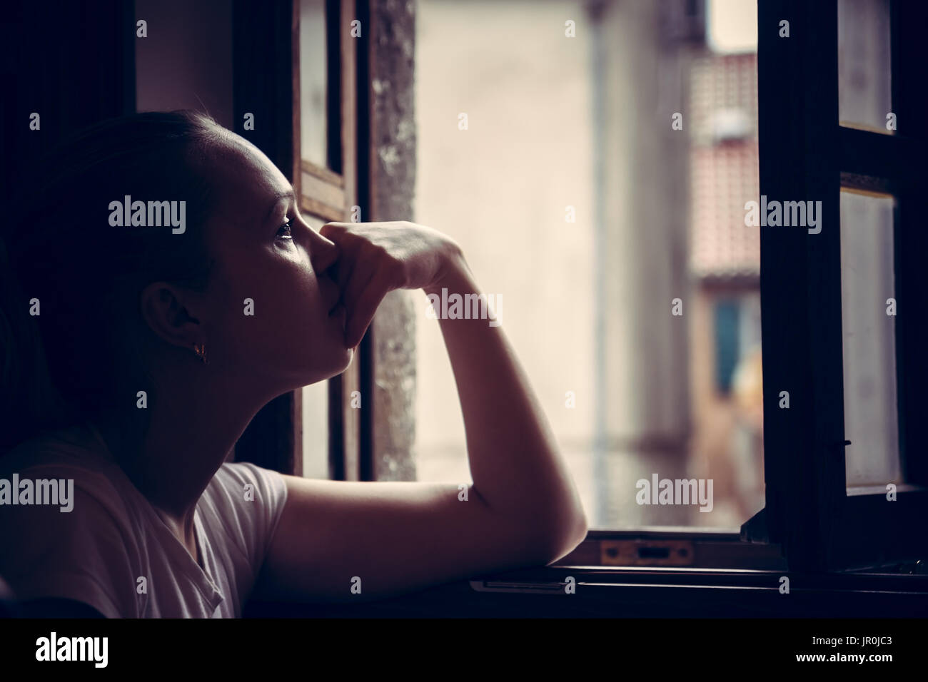 Pensive thoughtful young woman lost in thoughts dreaming and looking in opened  window in vintage style with dramatic mood - Stock Image