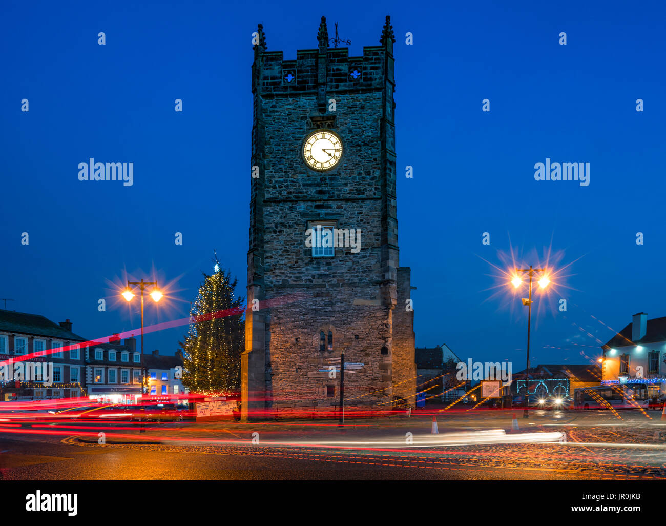 The Clock In A Tower And Lamp Posts Glow With Illumination At Dusk, With Light Trails On The Street; Richmond, Yorkshire, England - Stock Image