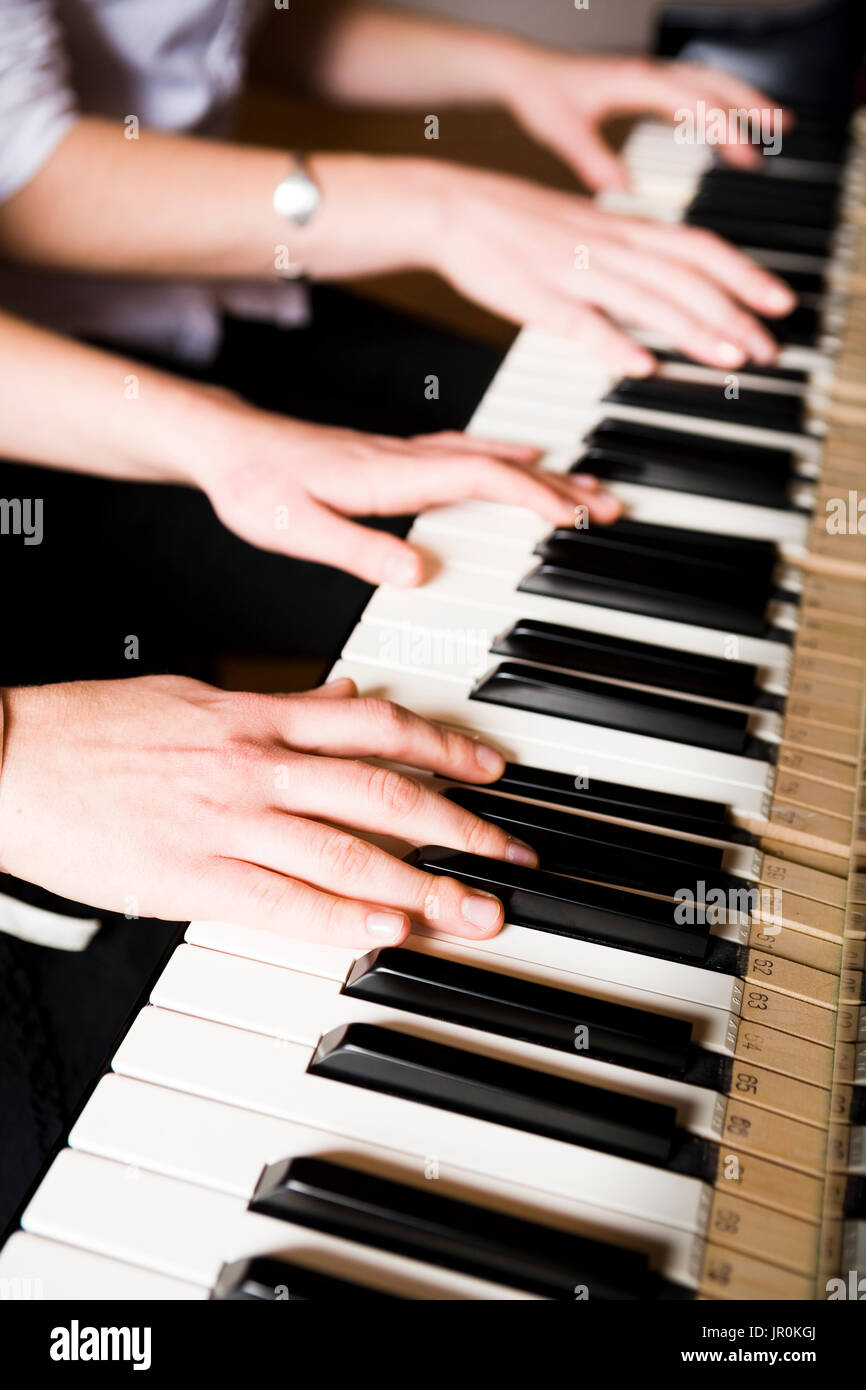 Playing A Duet On The Piano; Alaska, United States Of America - Stock Image