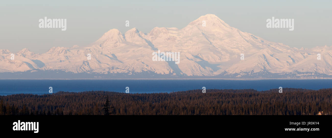 Snow Covered Mountains Range In The Distance With Ocean And Forest In The Foreground; Alaska, United States Of America - Stock Image