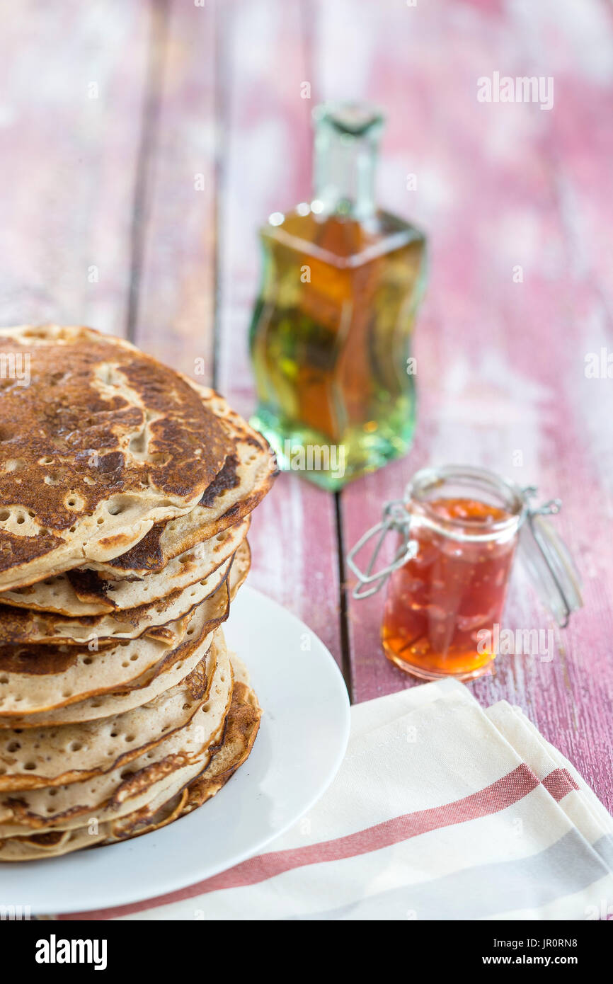 Glutten-free pancakes with jam and Maple syrup, bio healthy ingredients, on kitchen background - Stock Image