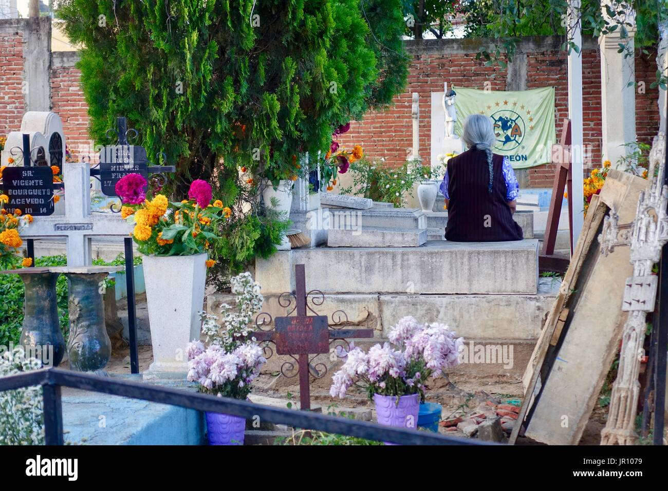 Elderly woman with long gray brain, back to camera, sits in contemplation on raised grave stones in cemetery during Muertos. Oaxaca Centro, Mexico. - Stock Image
