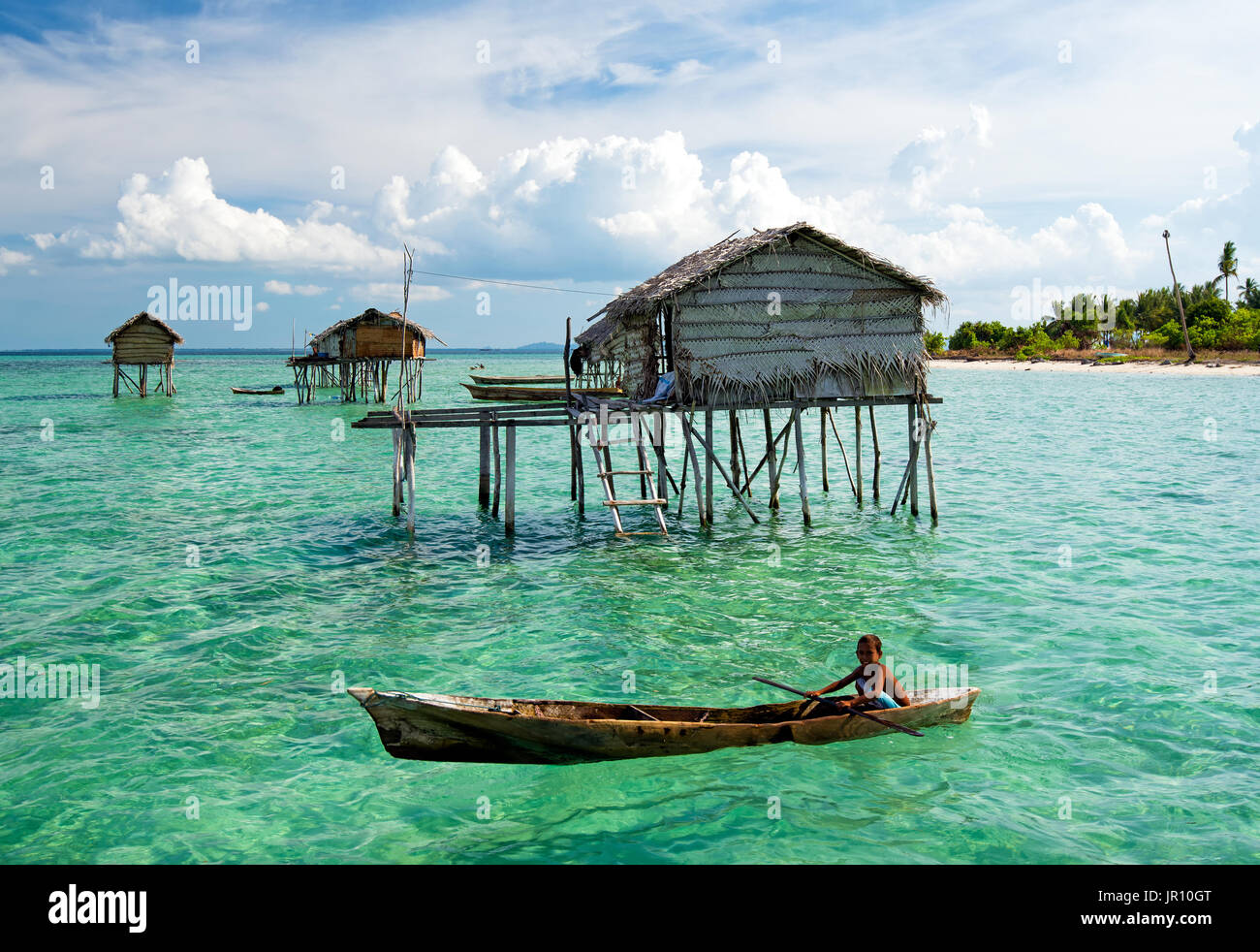 Semporna, Malaysia - 18 April, 2015: Young Bajau laut boy paddling a boat near stilted houses off the coast of Borneo Stock Photo