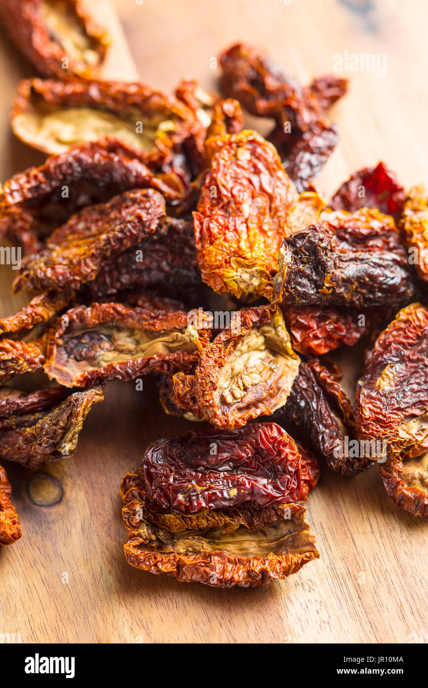 Dried sliced tomatoes on wooden table. Tomatoes as superfood. - Stock Image