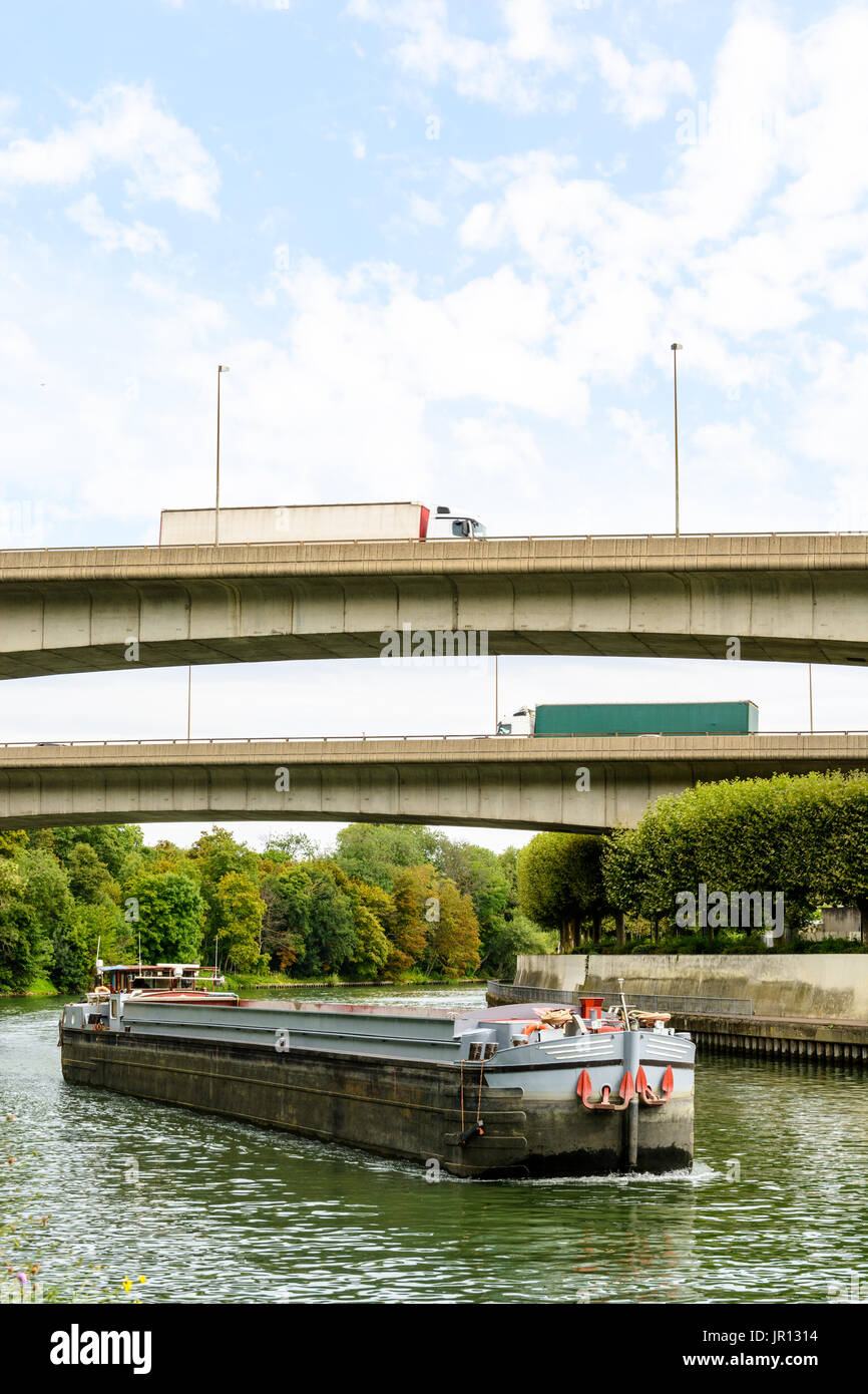 An empty cargo barge going down the river Marne toward Paris while semi-trailers trucks drive on the ramps of the Stock Photo