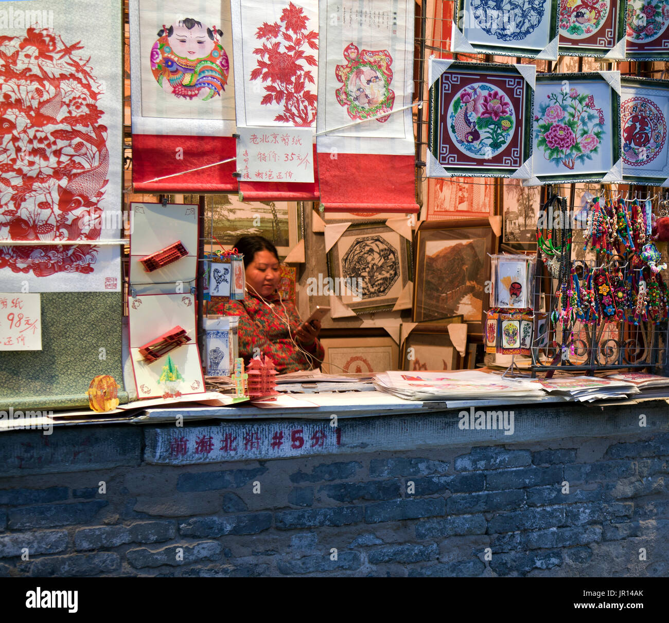 Woman on her cell phone at art souvenir stand, Shichahai (Houhai) Entertainment District at Twilight, Beijing, China. Stock Photo