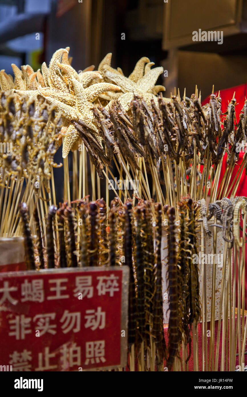Night Market, Beijing, China. Starfish on a skewer? Bugs?  Centipedes? Scorpions?  Such 'delicacies' await brave foodies in some of Beijing's night ma - Stock Image