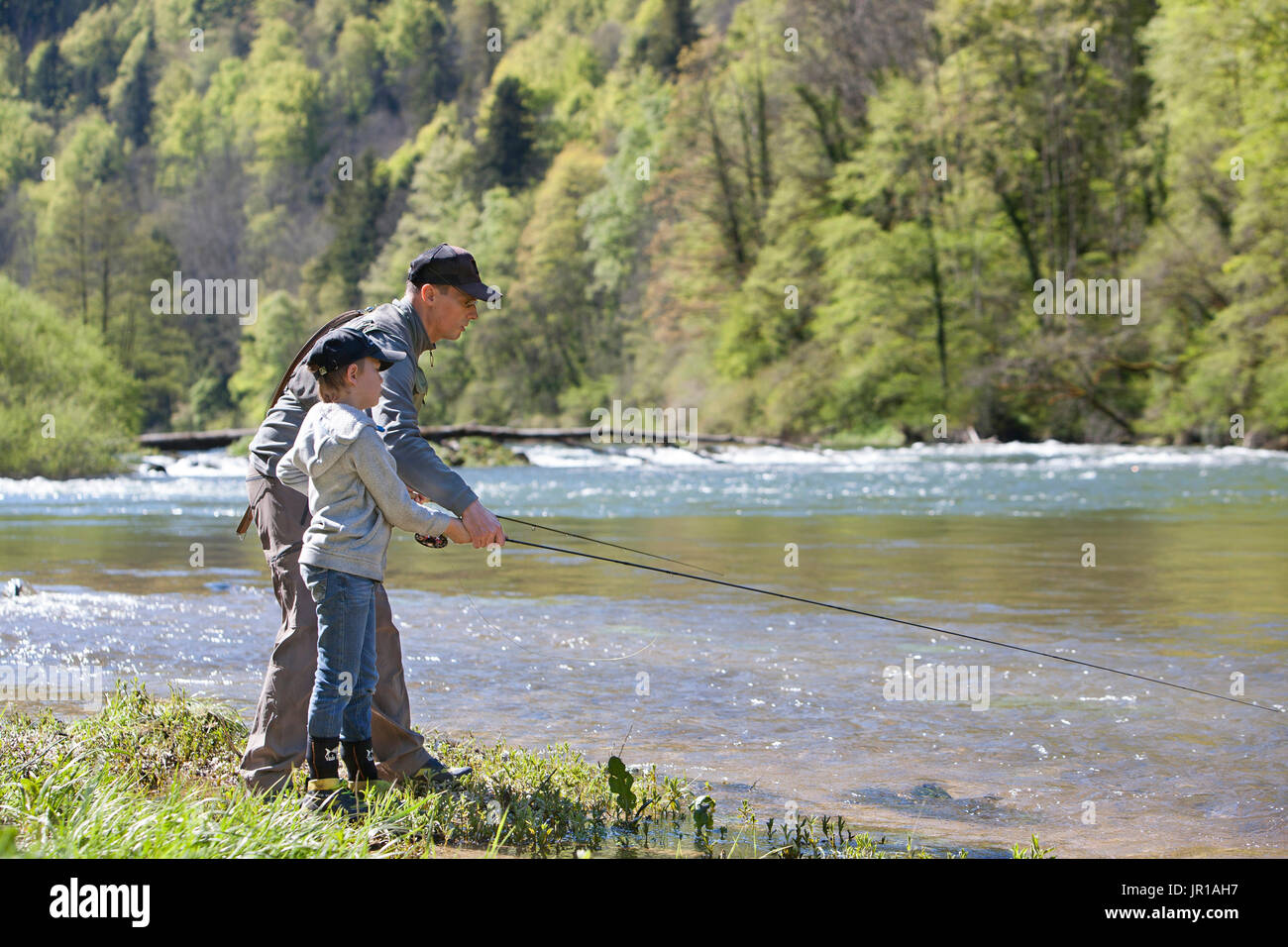 Fly fisherman and child learning, River Doubs, Goumois, Franche-Comte, France - Stock Image