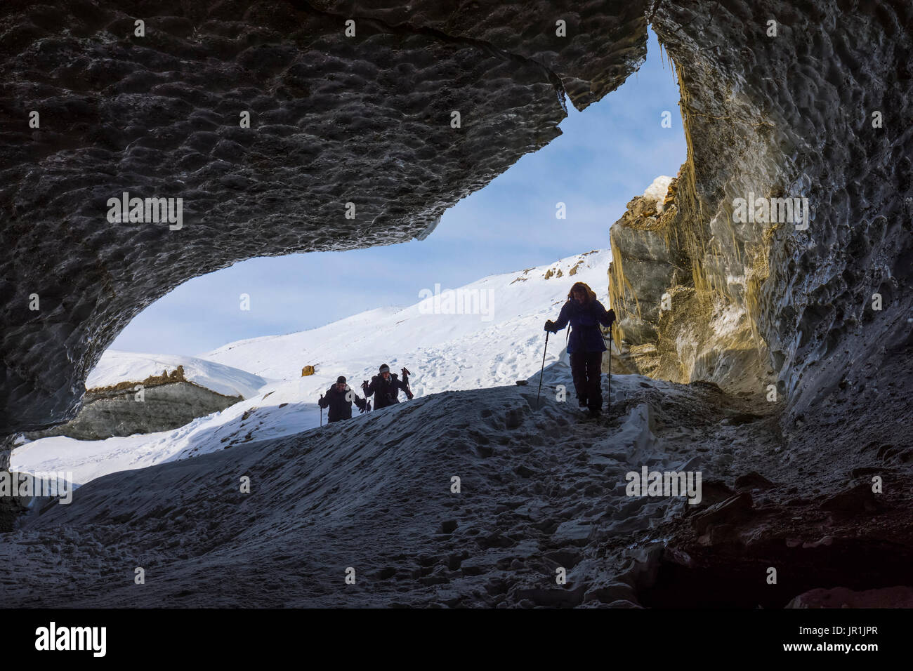 Hikers Enter An Ice Cave Within Castner Glacier In The Alaska Range. - Stock Image