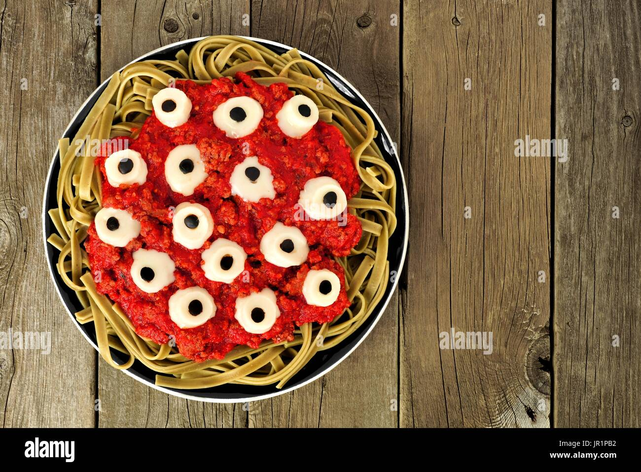 Halloween cheesy eyeball pasta with tomato meat sauce, above view over old wooden background - Stock Image