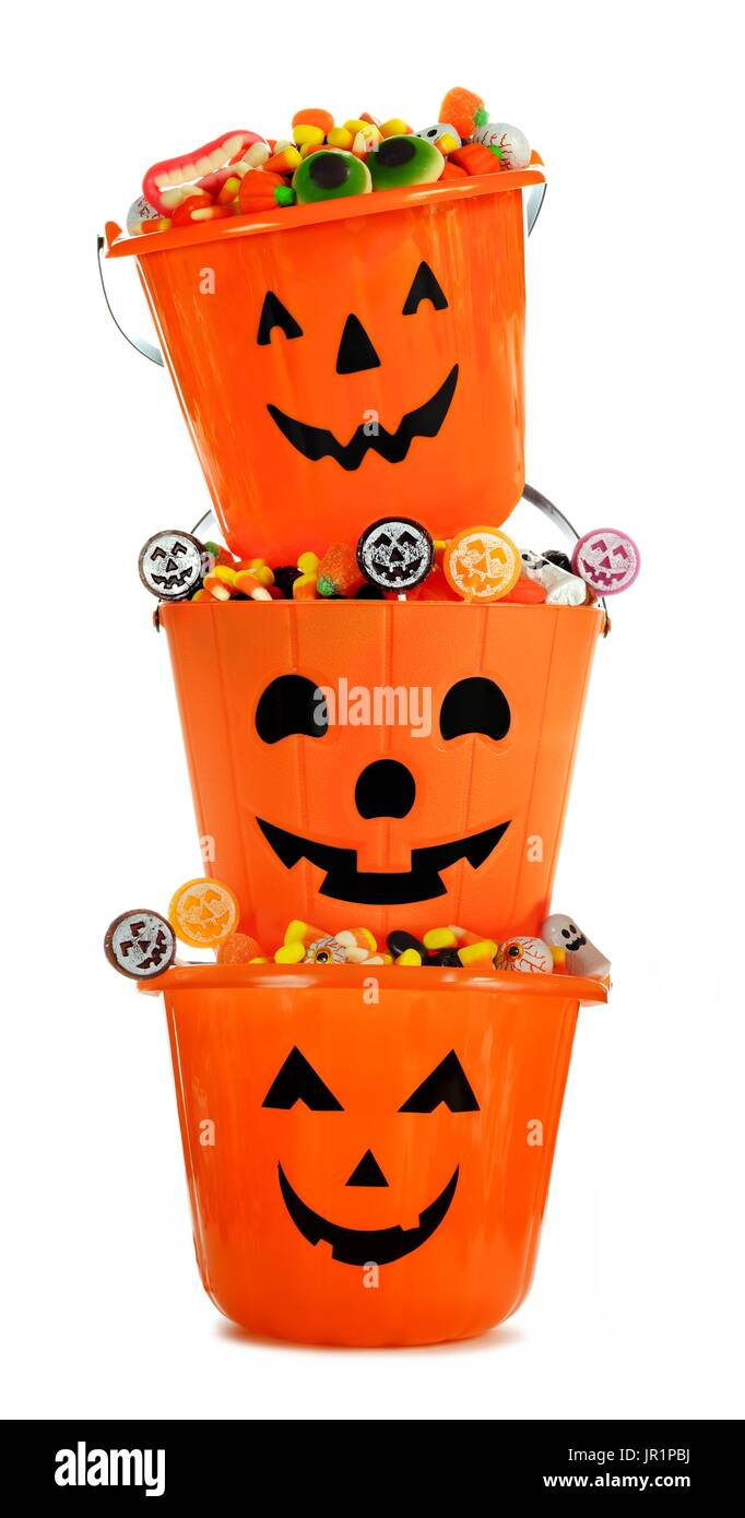 Halloween Jack o Lantern candy holders stacked and filled over a white background Stock Photo
