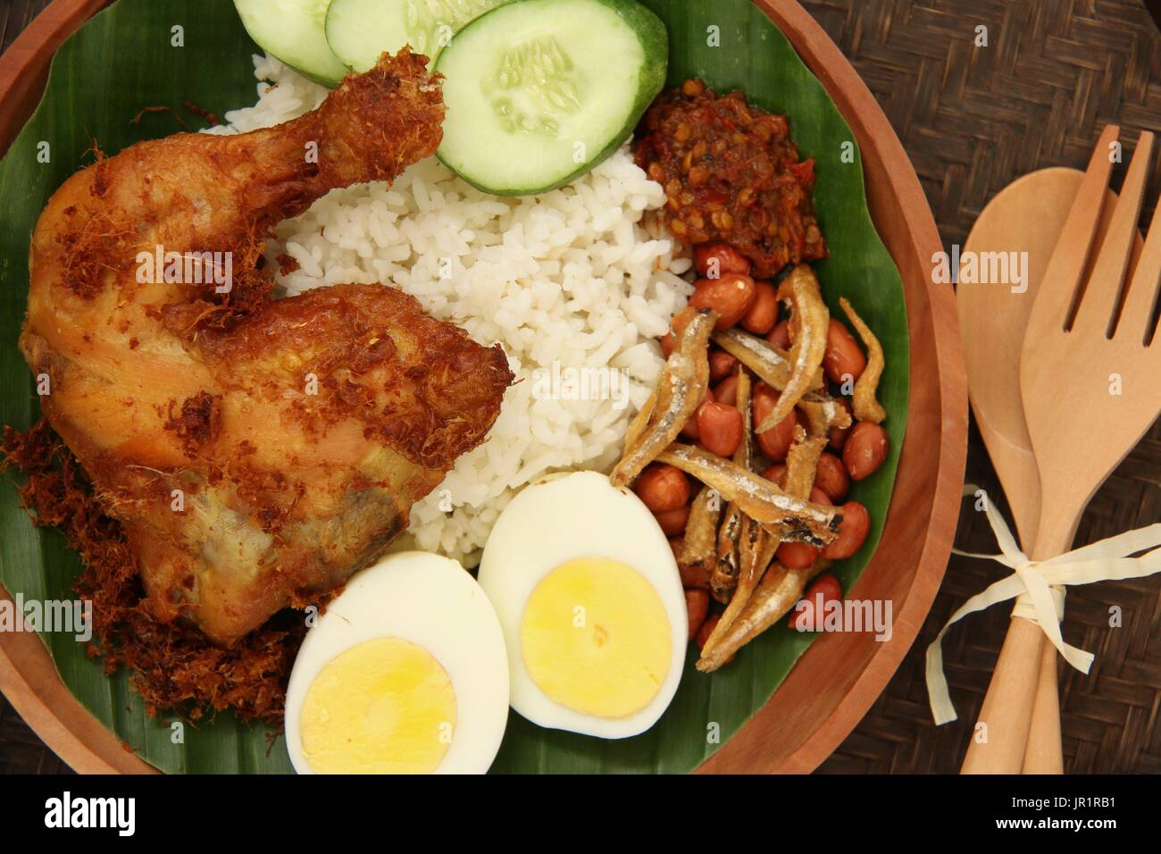 Nasi Lemak, Malaysian Savory Rice Dish with Fried Chicken, Egg, Peanuts, Anchovies, and Chili Paste - Stock Image