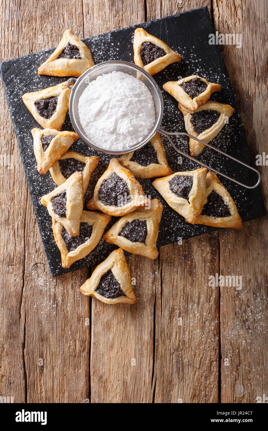 Hamentashen triangular cookies with poppy seed for Purim holiday close-up on the table. Vertical view from above - Stock Image