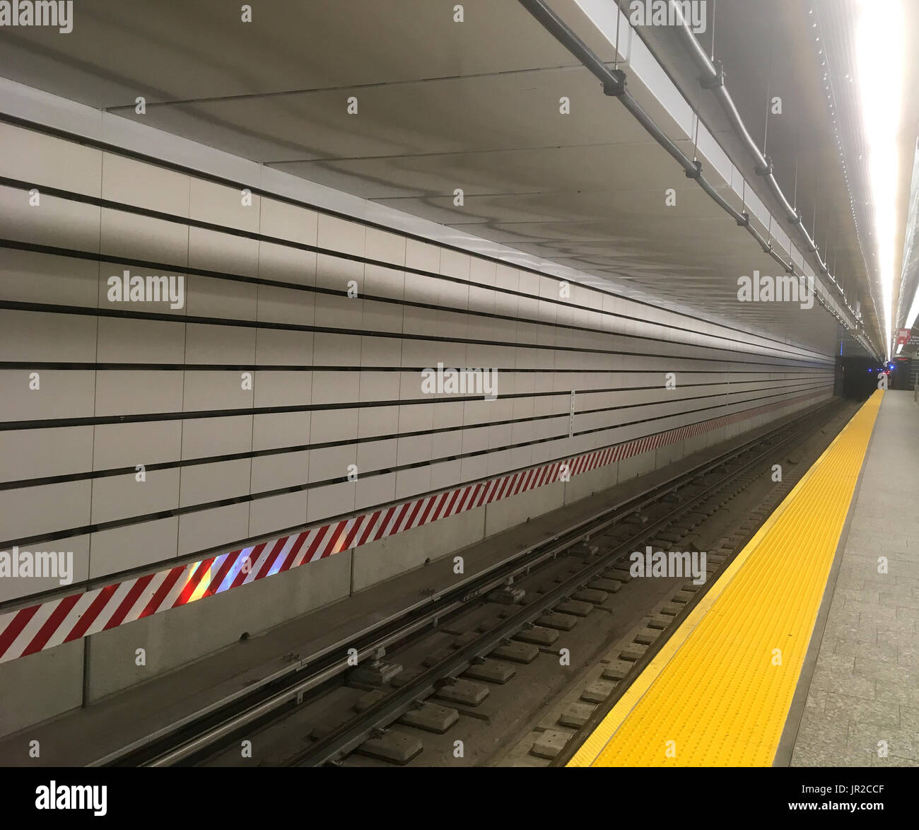 Long metro track stretching ahead new york city subway station with long metro track stretching ahead new york city subway station with white subway tiles red and white hazard warning and clear train tracks free of d dailygadgetfo Choice Image