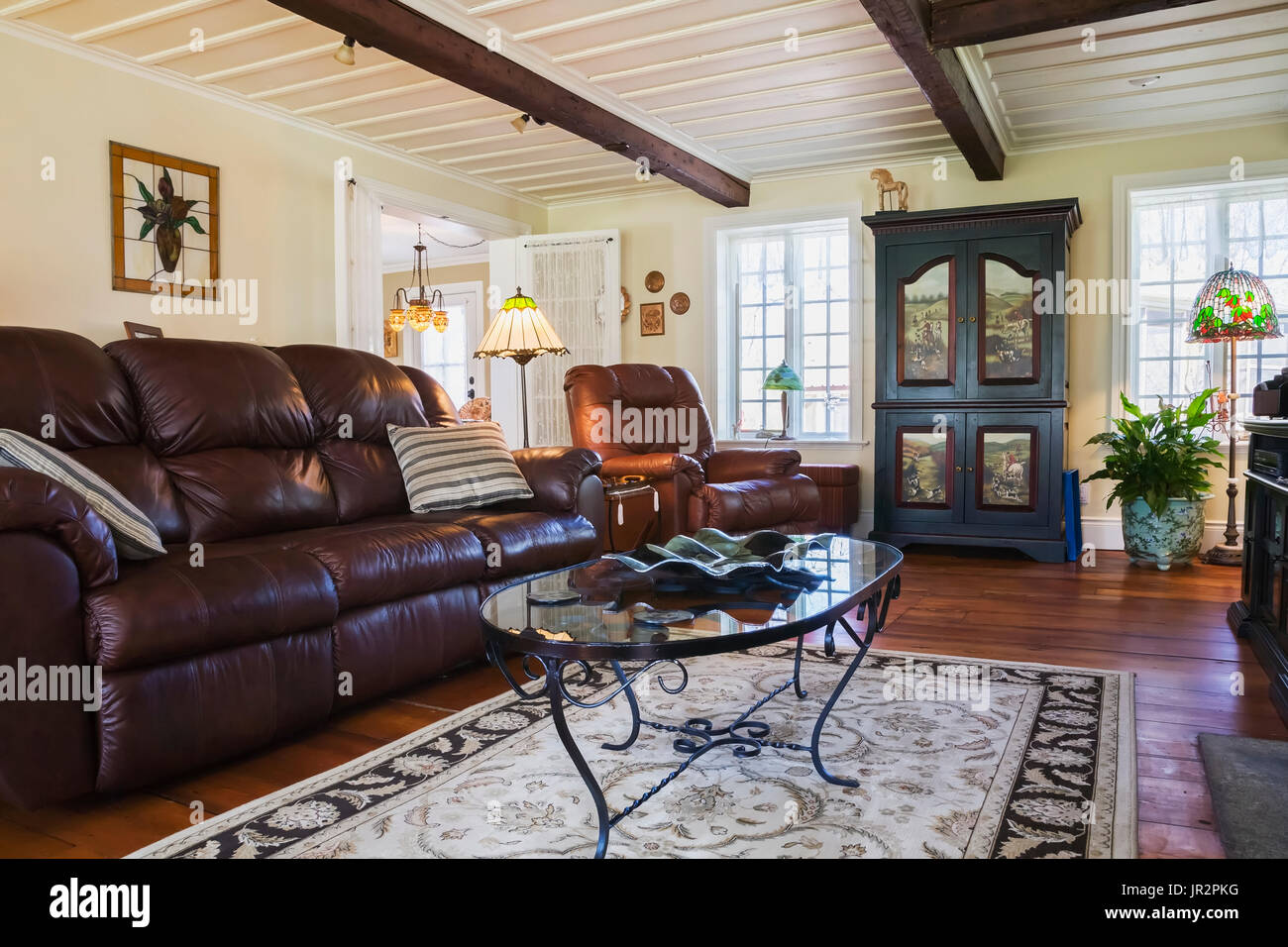 Brown Leather Sofa, Chair And Wooden Armoire In The Living Room ...
