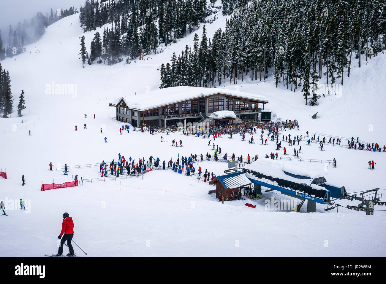 Downhill Skiiers At A Ski Resort Waiting In Line For The Chairlift; Whistler, British Columbia, Canada - Stock Image