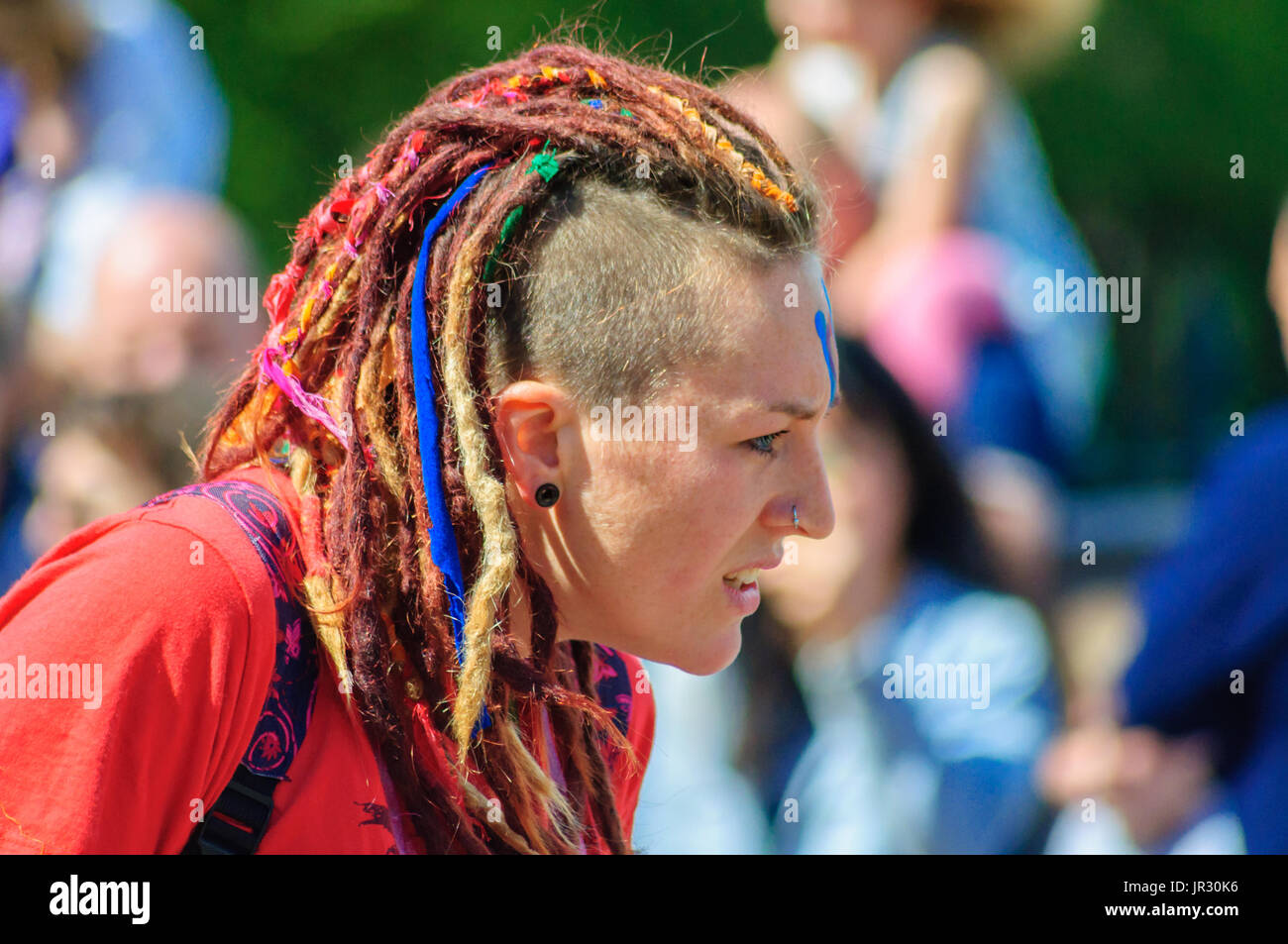 Female performer with shaved and dreadlock hairstyle in Edinburgh during the Carnival of The Jazz and Blues Festival - Stock Image
