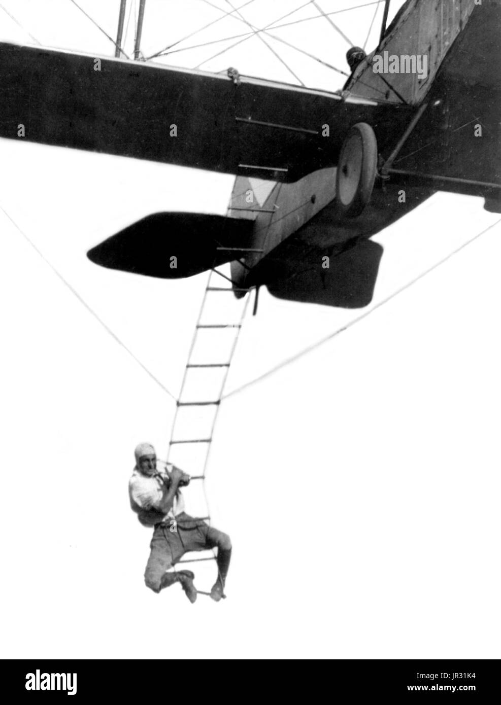 'Fearless Freddie', a Hollywood stunt man, clinging to a rope ladder slung from a plane flown by A.M. Maltrup, about to drop into automobile below: automobile not shown. Fredrick M. Lund (August 11, 1897 - October 3, 1931) American daredevil. When WWI was declared, he joined the Air Service and trained at San Antonio. He was sent to the 4th Pursuit Squadron at Toul, France. Stricken with tuberculosis following the war, he returned to the states, got back his strength and joined the Gates Flying Circus as a stunt flyer, working for a while in Hollywood, as a movie double, where he earned the ni - Stock Image