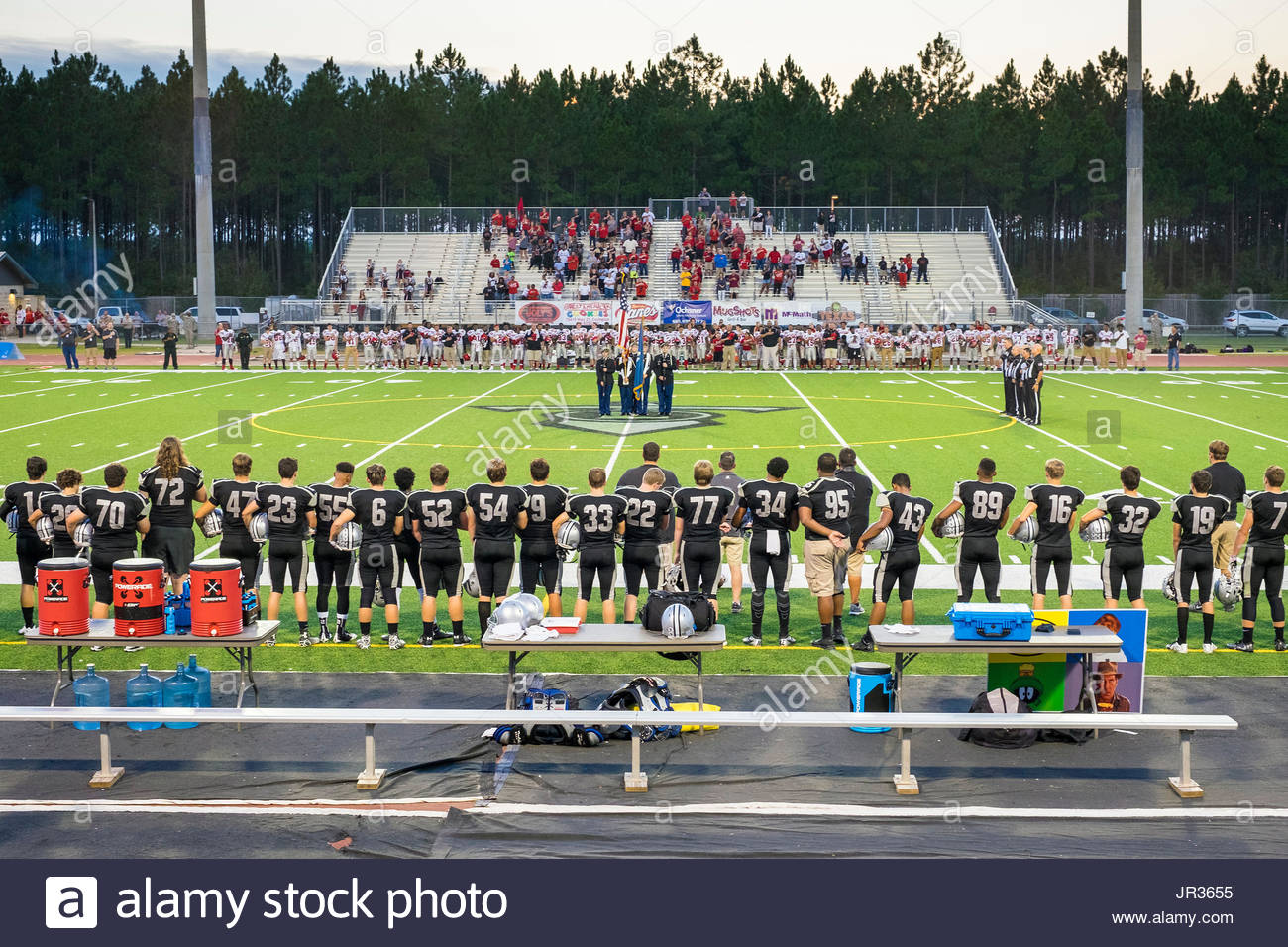 High school football game, teams standing for the national anthem, Lacombe Louisiana, United States - Stock Image