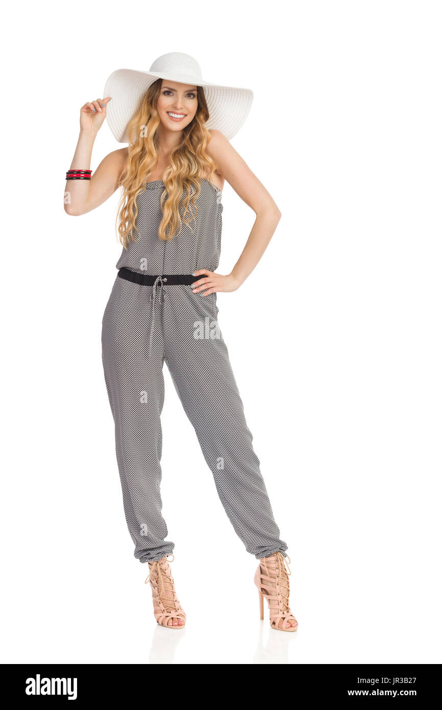 Beautiful young woman in dotted jumpsuit, white sun hat and high heels is standing with legs apart and looking at camera and smiling. Full length stud - Stock Image