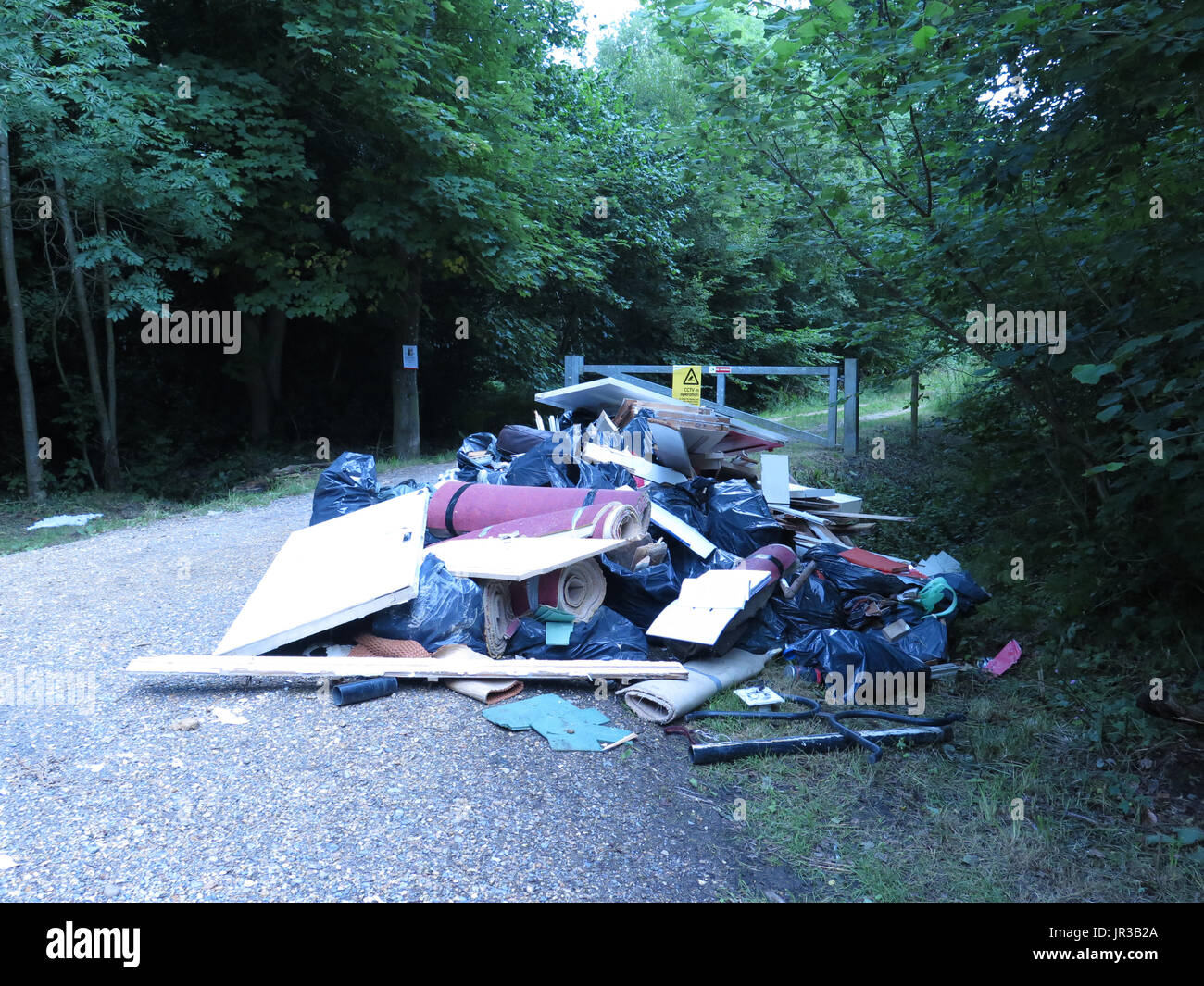 fly tipping under CCTV sign - Stock Image