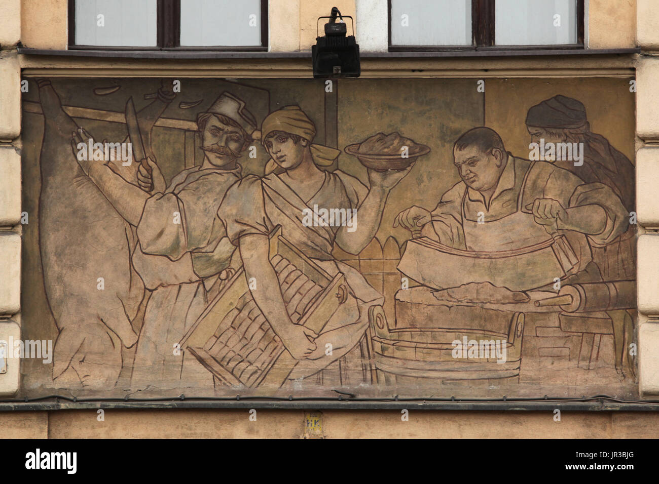 Pig slaughter depicted in the mural painting by Czech painter Ladislav Novák devoted to the Prague Butchers Guild on the dwelling house designed by Czech architect Jan Zeyer in Argentinská Street in Holešovice district in Prague, Czech Republic. - Stock Image