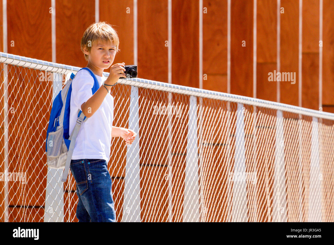 Boy with digital camera taking pictures outdoor in the city - Stock Image